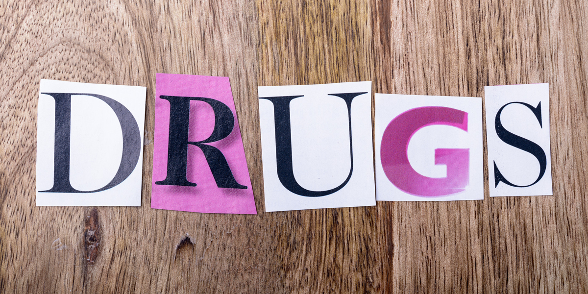 the word DRUGS spelled using magazine clippings on a hardwood background