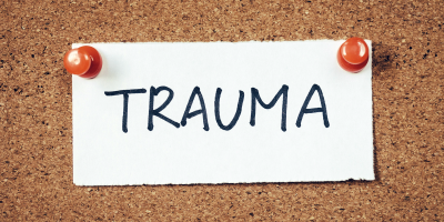 the word TRAUMA hand-printed on a piece of paper attached to a bulletin board with pushpins