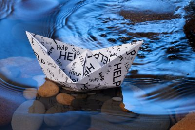 floating paper boat inscribed with the word HELP