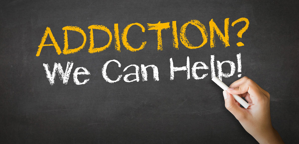 a hand on chalkboard writing the words Addiction? We Can Help!