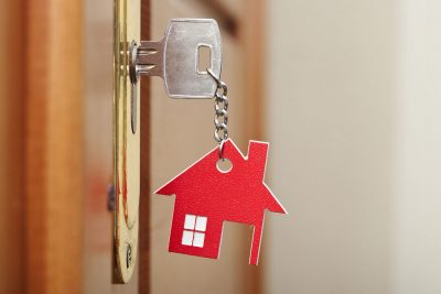 key in house door lock with a house shaped keychain