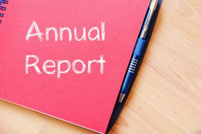 Annual report text concept written on notebook with pen