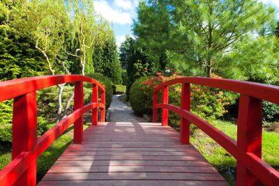 re bridge leading to lush gardens on a sunny day