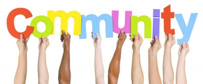 several hands holding up colourful letters to spell the word community