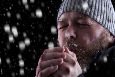 man blowing on hands to stay warm