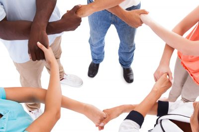 diverse group of friends standing in a circle with joined hands