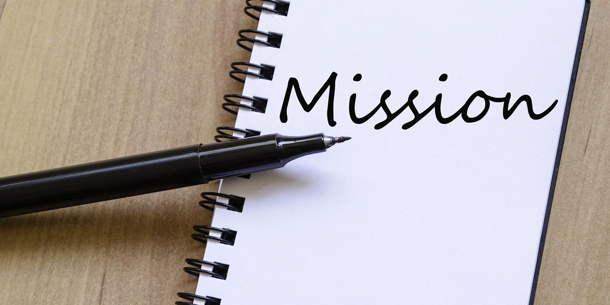 spiral notepad with the word mission on it with a pen on top