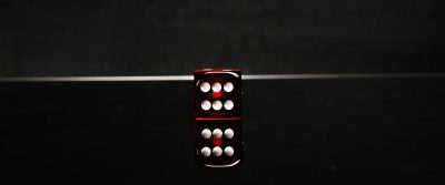 single dice on black glossy game table