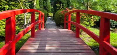 red bridge leading to lush gardens on a sunny day
