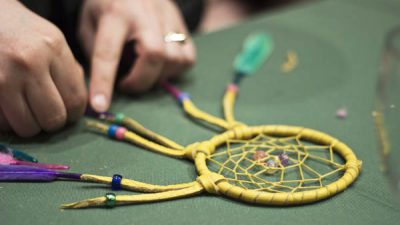 hands assembling a dream catcher