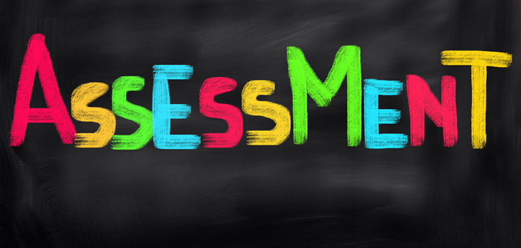 the word assessment printed on a chalkboard in multi-coloured chalk