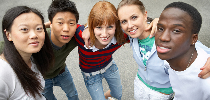 group of teenagers arm-in-arm on a sidewalk