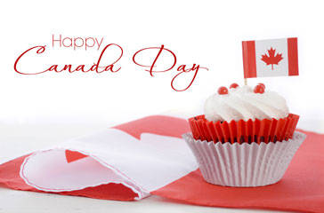 cupcake with Canada Day mini flag in icing set on top of a fabric Canada flag