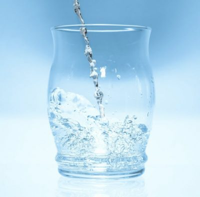 water pouring into a clear glass