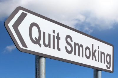 Quit Smoking road sign against blue sky with fluffy clouds
