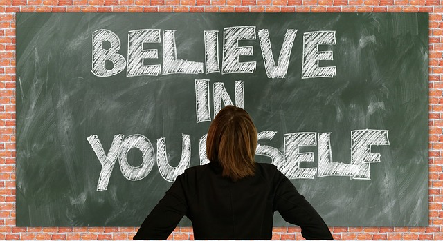 "woman standing in front of blackboard with the message ""Believe in Yourself"""