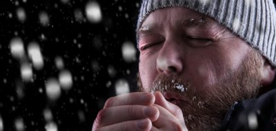 man in toque blowing warm air on hands
