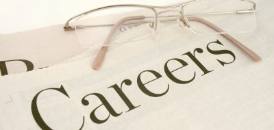 pair of reading glasses laying on top of the career section of a newspaper