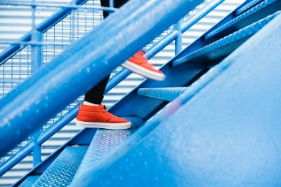 person in bright orange sneakers walking up a flight of stairs
