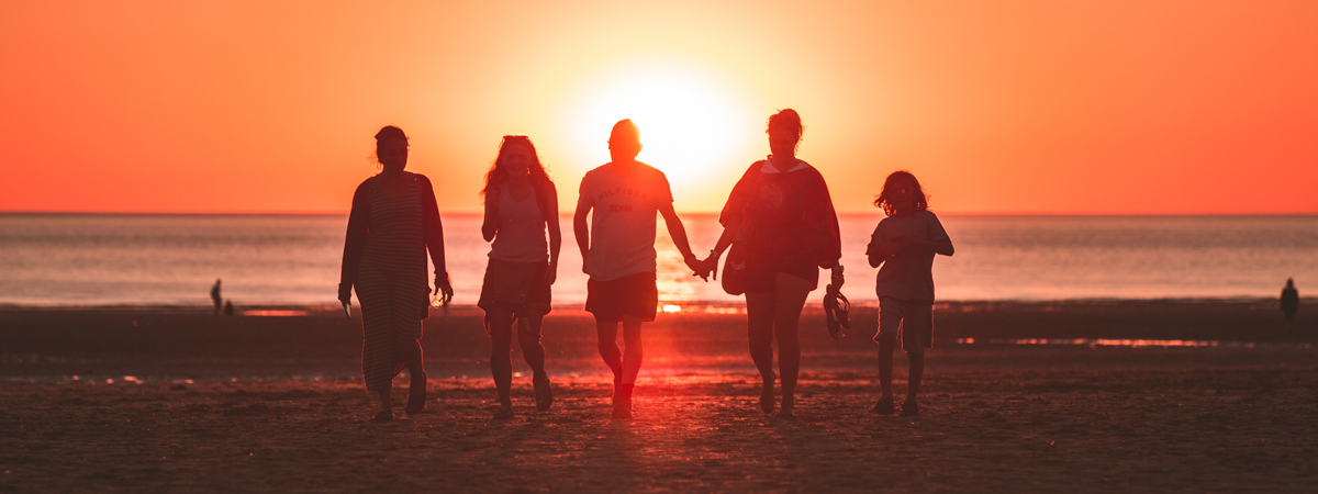 family strolling along beach hand-in-hand at sunset