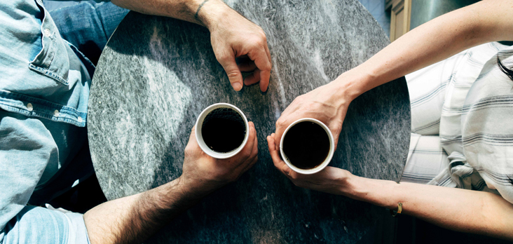 man and woman sitting at bistro table with hands wrapped around coffee