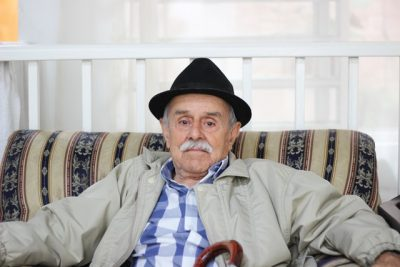 elderly man sitting on a couch with his cane in his lap