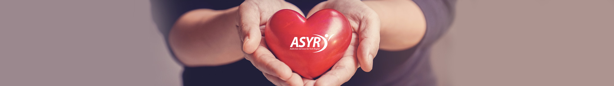 woman cradling a red heart in her hands with ASYR logo imprinted on it