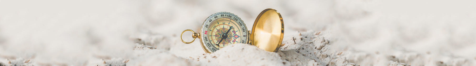 compass resting on sand