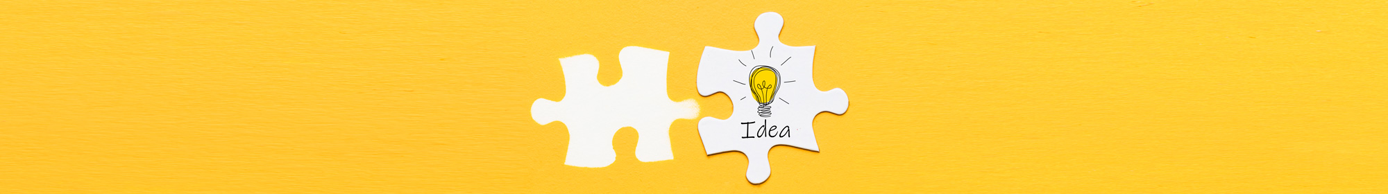 two wite puzzle pieces with an idea light bulb on yellow background